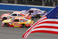 Oct. 11, 2009. Auto Club Speedway, CA: Joey Logano noses past Kevin Harvick and Clint Boyer with the American flag in the foreground.