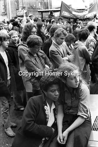 Whitechapel, London. 1978<br /> At the junction of Brick Lane and Bethnal Green Road during the summer the Socialist Workers Party organised regular Saturday Anti Nazi League demonstrations, against the National Front, who in turn each Sunday held their meetings and distributed their newspapers from the same place. A young women proudly wears badges proclaiming &ldquo;Gays Against the Nazis&rdquo;, &ldquo;Right to Work&rdquo;, &ldquo;Skateboard Against Racism&rdquo;, &ldquo;Anti Nazi League&rdquo; and the Star of David.