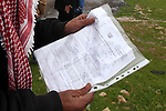 A Palestinian Bedouin man hold an Israeli notice to demolish his tent in the village of Jaba' southern the West Bank city of Ramallah on Jan. 31, 2013. Israeli forces handed notices ordering the demolition of 16 houses in the village of Jaba', for settlement expansion works in the nearby Jewish settlement of Adam. Photo by Issam Rimawi