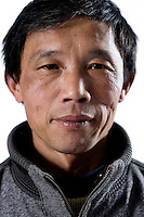 """Worker Wang Congming poses for a photograph in Artissmo Designs factory in Yiwu, Zhejiang province, China, on February 14, 2012. Wang Congming, 48-year-old, from Chongqing, is married to Xu Yuqing, is the father of Wang Song, and works with them in the same factory: """"I left my previous job because I had to work outside, under the sun or the rain, for 9 hours a day. I make more money here, 3,000 RMB a month (360 euros)"""". Photo by Lucas Schifres/Pictobank"""