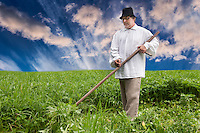 Farmer using scythe to mow grass traditionally in Estonia. Dramatic clouds, sky scenic.