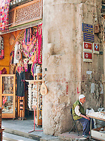 A man sits at his stall on a street in the Old City of Damascus, Syria