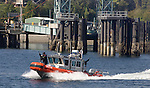 A United State Coast Guard Patrol boat passes the Southworth Ferry Terminal while providing  escort service for the Washington State Ferry System in Seattle on August 20, 2009.  The personnel and boats, from the 13th Coast Guard District, provide protection from possible terrorists attacks in support of the Homeland Security for ferries operating from Seattle area ferry terminals to those on the Kitsap Peninsula, Vashion Island, and Bainbridge Island.    © 2009. All Rights Reserved. Jim Bryant