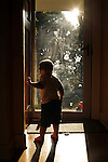 My son Sam, age two, stands in the doorway of his Springfield, Illinois home on a summer evening.