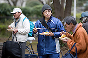 Homeless men eat a free lunch given to them at a soup kitchen, run by a Korean Christian church, in Ueno Park, Tokyo, Japan, Friday 27th March 2009. The men, most of whom are long term homeless, attend the soup kitchen 4 times a week, and have to listen to a church sermon prior to being given a hot lunch, food to take away, and if they wish they can have haircuts, and obtain clothes.