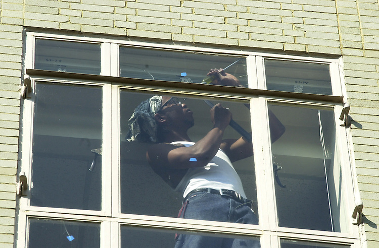 2safeglass100301 -- The Ford House Office Building, at 3rd and D St. SW, has had some of its' windows prepped for a shatter-resistant film, for fear that a bomb's explosion could cause flying shards of glass to injur employees inside the building.  Here, a worker cleans a payne before the window is treated.