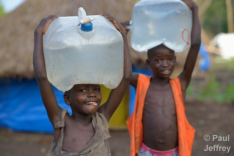 Children carry water in a camp for for than 5,000 displaced people in Riimenze, in South Sudan's Gbudwe State, what was formerly Western Equatoria. Families here were displaced at the beginning of 2017, as fighting between government soldiers and rebels escalated.<br /> <br /> Two Catholic groups, Caritas Austria and Solidarity with South Sudan, have played key roles in assuring that the displaced families here have food, shelter and water.<br /> The camp formed around the Catholic Church in Riimenze as people fled violence in nearby villages for what they perceived as the safety offered by the church.