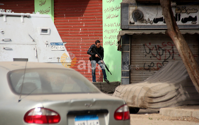 A member of Egyptian security forces takes position in Mataryah destrict, in Cairo on January 25, 2015. A protester was killed in Egypt and a bomb wounded two policemen on Sunday, the anniversary of the 2011 uprising that toppled Mubarak, security sources said. Photo by Amr Sayed