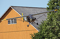 Piper L-18C Super Cub LN-ACJ coming in to land in a field near a farm.<br /> <br /> Airplanes and reenactors photographed at in connection with H&oslash;ytorptreffet, an annual event at the H&oslash;ytorp fort. <br /> <br /> H&oslash;ytorp fort is a barrage fort in the Glomma defence line, built 1912-17. On April 13th and 14th 1940 the fort was in combat against German army units . It is now protected as a national monument.<br /> <br /> &copy;Fredrik Naumann/Felix Features