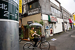A man cycles past a collection of bars in Shimokitazawa in Setagaya Ward, Tokyo, Japan..Photographer: Robert Gilhooly