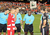 Carey Talley #8 of D.C. United and Daniel Hernandez #2 of FC Dallas with referee Abiodun Okulaja during an MLS match against FC Dallas at RFK Stadium in Washington D.C. on August 14 2010. Dallas won 3-1.