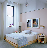 A pair of contemporary photographic portraits hangs above the platform bed in this tranquil bedroom