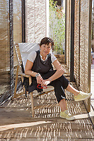 The stylist Lurdes Bergada sitting in a deck chair in the entrance hall to her new home