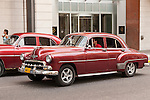 Havana, Cuba; a pair of red, classic 1952 Chevy cars, serving as taxis, along the street in Havana