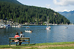 Couple seated looking at boats moored at  with the trees of the Cove forest in the background. Deep Cove, Burrard Inlet, Vancouver, British Columbia, Canada.