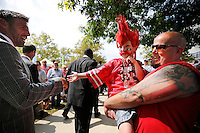 Coach Mike Vrabel high fives Dylan Hershberger, 6, being held by his dad Joe Hershberger of Dalton, Ohio as the team walks into the Skull Session prior to the NCAA football game against San Diego State at Ohio Stadium in Columbus on Sept. 7, 2013. (Adam Cairns / The Columbus Dispatch)