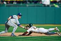 OAKLAND, CA - Rickey Henderson of the Oakland Athletics runs the bases and steals second base as Toronto Blue Jays second baseman Roberto Alomar takes the throw during Game 3 of the American League Championship Series at the Oakland Coliseum in Oakland, California in 1992. Photo by Brad Mangin