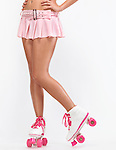 Closeup of legs of a young woman wearing a pink mini skirt and classic roller girl derby skates isolated on white background