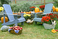 Roadside stand for fruit, veges, and flowers. Two Blue adironack chairs sit near road and stone wall, in October, Vermont USA