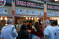 People buying Dim Sum snacks at a food stall at the night market in Chinatown, British Columbia, Canada