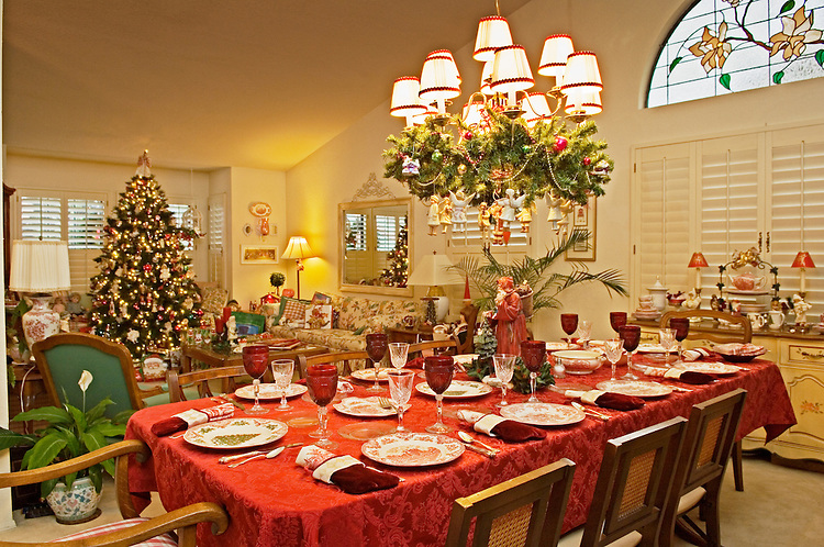 dining room table set for christmas dinner with tree decorations and