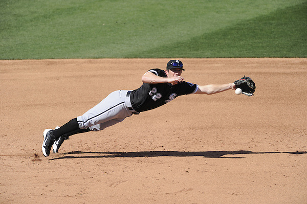 GLENDALE, AZ - MARCH 08:  Brent Morel #22 of the Chicago White Sox dives but cannot catch the ball against the Texas Rangers during a spring training game on March 8, 2012 at Surprise Stadium in Surprise, Arizona.  The White Sox defeated the Rangers 6-3.  (Photo by Ron Vesely)  Subject:  Brent Morel