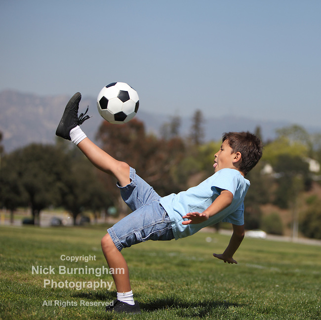 "A young boy performs a soccer ""bicycle kick"" in a park"
