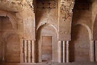 Qasr Kharana, desert castle, Jordan. This room has a vaulted ceiling, pilasters, wall arches, carved roundels above the doorway and shows a Sassanid influence. This building was built c. 710 in the early Umayyad period under the Caliph Walid I although its purpose is unknown. It did not have a military function. It is a square building with small projecting corner turrets and a projecting round entrance seen here on the South side. It has 60 rooms inside over two floors around a central courtyard where rain is collected. The small slit windows are for light and ventilation. It fell out of use and was damaged by several earthquakes before being rediscovered in 1901 and restored in the 1970s. Picture by Manuel Cohen