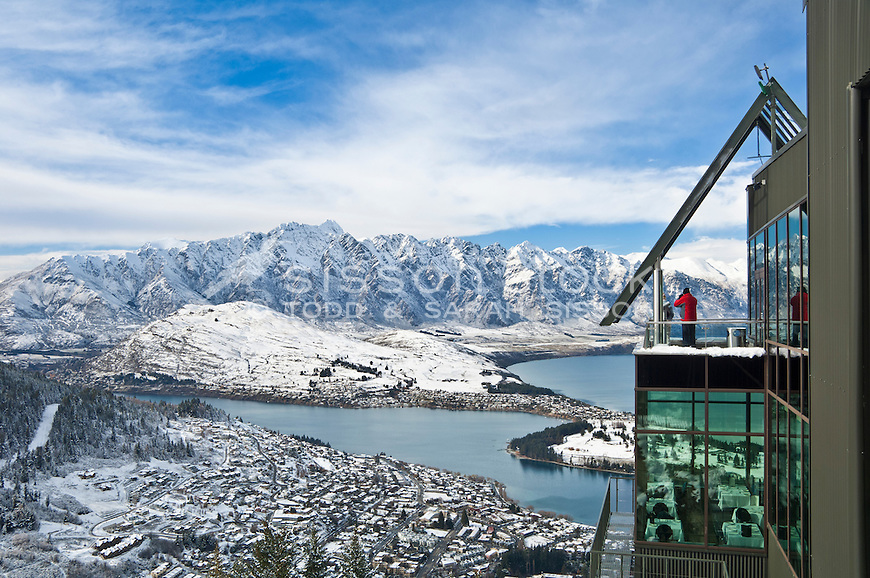 Tourist looks out at winter snow on Queenstown and the Remarkables from Skyline Gondola Restaurant, Central Otago, South Island, New Zealand