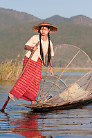 Myanmar, Burma.  Young Burmese Woman Rowing with one Leg, Looking for a Place to Set her Fishing Net.  Inle Lake, Shan State.  She is wearing thanaka paste on her cheeks, a Burmese cosmetic sunscreen.