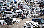 A man looks through hundreds of cars wrecked by the March 11 quake and tsunami in  Miyako, Iwate Prefecture, Japan on  3 April 2011. Authorities are unable to dispose of much of the debris created by the March disasters due to fears of radiation contamination, leading to giant mounds of waste that are becoming increasingly more toxic. Photographer: Robert Gilhooly