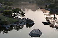Mist rising from the water at sunrise on the ornamental lake of the Suizen-ji garden
