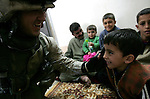 After a house to set up a supporting position, a Marine with Golf Company 2nd Battalion 5th Marines lets a Iraqi boy listen to his radio while comrades in the street hunt insurgents who ambushed their patrol in Ramadi on January 20, 2005..