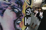 Standing beside a 'manga' illustration banner, a woman eats some fruit in the Ameyokocho market street, near Ueno, Tokyo, Japan.