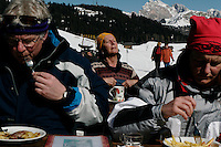 Skiers eat and sun at a restaurant in the Siusi ski area of the Dolomites in Italy.    The restaurant is owned by the Daniel family and they have cows in the same area in the summer.