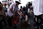 A poor woman begging at a market on March 20, 1997 in central Phnom Penh, Cambodia..Thousands of poor people come from the country side to look for work in the capital. A lot of them live on the streets. .(Photo: Per-Anders Pettersson/ Liaison Agency)