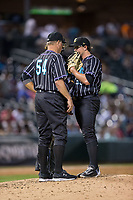 Charlotte Knights pitching coach Steve McCatty (54) has a meeting on the mound with starting pitcher Carson Fulmer (28) during the game against the Norfolk Tides at BB&T BallPark on May 2, 2017 in Charlotte, North Carolina.  The Knights defeated the Tides 8-3.  (Brian Westerholt/Four Seam Images)