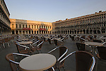 Chairs and tables at outside street café early morning. St Marks square Venice, Italy.