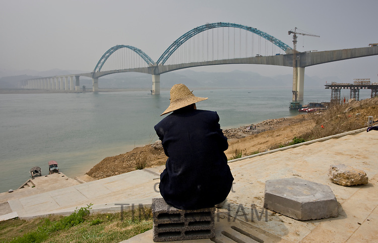 Man watches construction of a railway bridge in Yichang, China