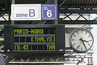 A station clock, train schedule board indicating Thalys departure time, and zone board on track six in Brussels-South Station.