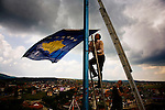 Raising the new Kosovo flag above Shtime, a city where devestating violence took place during the war in '99.