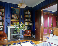 A traditional bedroom with blue striped wallpaper. Two leather tub chairs stand either side of a fireplace. An open door gives a view to a dressing room beyond.
