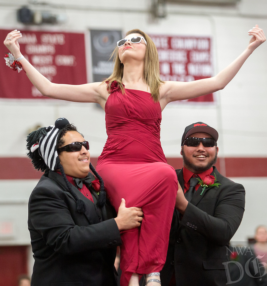NWA Media/JASON IVESTER --10/17/2014--<br /> Springdale seniors Carlos Lara (left) and Jose Ambriz carry senior Unity member Angelica Morales on their exit from the homecoming assembly on Friday, Oct. 17, 2014, in Bulldog Gym. The Bulldogs hosted Bentonville for their annual homecoming football game later that night.