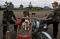 A street scenes in Khailino with dog in a side car and men dressed in camouflage.