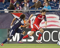 Toronto FC forward Alan Gordon (21) dribbles down the wing as New England Revolution defender Kevin Alston (30) defends. In a Major League Soccer (MLS) match, the New England Revolution tied Toronto FC, 0-0, at Gillette Stadium on June 15, 2011.