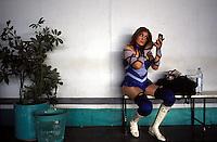 A luchadora applies make-up before a photo shoot in the Gymnasio Latinoamericano
