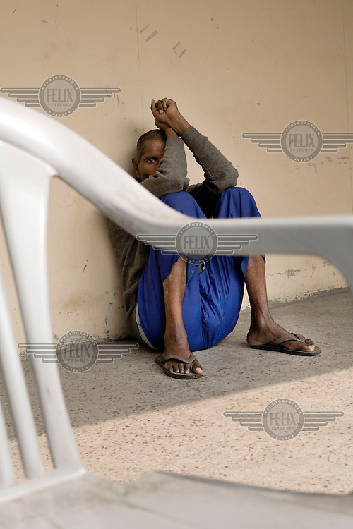 A mentally ill man sits in the yard of a secure ward at the Institute of Human Behaviour and Allied Sciences (IHBAS) in Delhi.