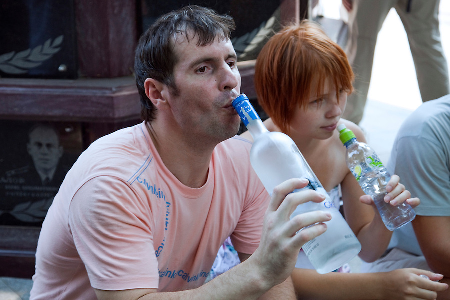 Moscow, russia, 25/07/2010..a man drinks vodka from the bottle as