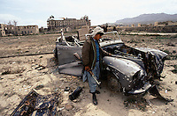 A Moudjahidin with what remain of the King Daimler DK400 car, in the courtyard of the Afghan Kabul National museum in Spring 1995. On the back left, the burn and loot national museum and on the right, the destroy Darulaman Palace.