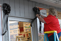 Debra Pancake hangs a black bow over the entrance of her gas station store in Buckhannon, West Virginia, Friday, Jan. 6, 2006, as the town mourns the death of 12 miners in an explosion in Sago on Monday. (Photo by Gary Gardiner)<br />